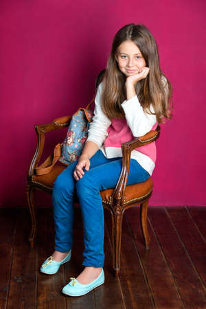 Teenage girl sitting on armchair on painted pink wall background smiling and waiting for something.