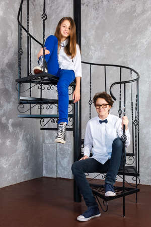Teenage girls wearing glasses and sneakers sitting on spiral staircase in loft apartment. Teenagers in white shirts posing in loft