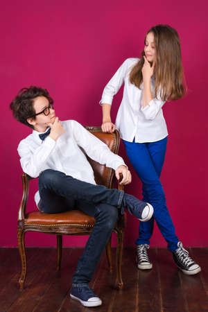 Teenage girls wearing jeans and sneakers posing on painted pink wall background in loft apartment. Teenagers in white shirts posing in loft