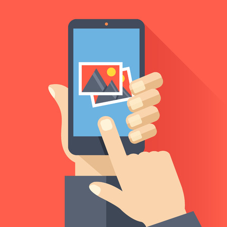 cellphone in hand: Hand holds smartphone with photos icon on smartphone screen. Multimedia, photo album app concept. Creative flat design vector illustration