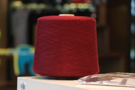 Dark red color yarn is waiting for starting for the production process, with soft background.