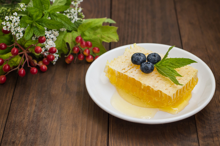 Honeycomb with blueberries and mint. Wooden background