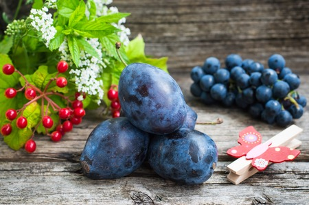 Plums with grapes on a wooden background.