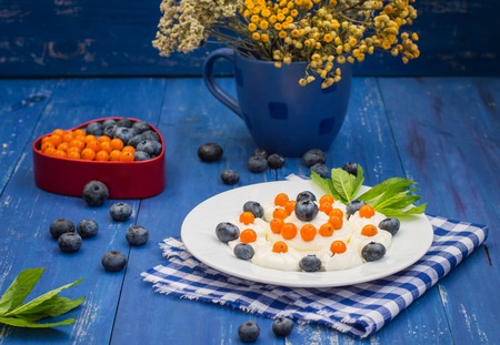 Blueberries and buckthorn laid out in the shape of a heart with cream meringue