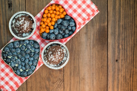 Blueberries and buckthorn laid out in the shape of a heart and chocolate truffles Stock Photo