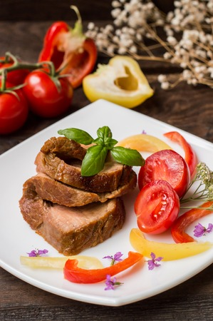 meatloaf: Cooked Sliced meatloaf with tomato, pepper and basil. Wooden background