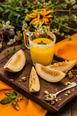 field mint: Fresh and ripe melon and fresh juice. Wooden background.