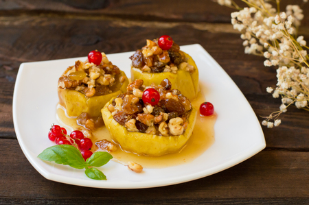 Baked apples with raisins, walnuts and honey for dessert. Wooden rustic background