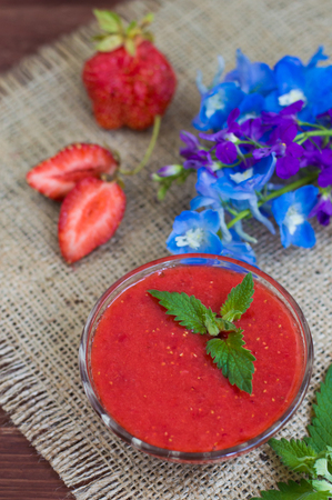 lemon balm: Strawberry jam with lemon balm on a wooden table, against a background of burlap