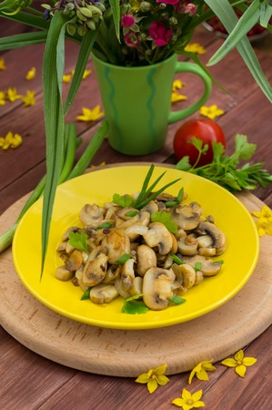 Fried mushrooms on a yellow plate. Wooden background.