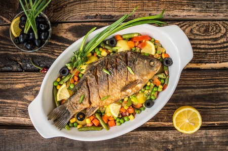 Grilled fish with steamed vegetables. Wooden background