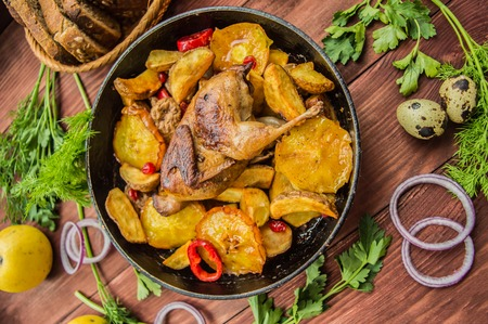 Quail baked in a pan with potatoes and apples. On a brown wooden background. Top view