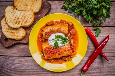 filled roll: Dinner with cabbage rolls in tomato sauce decorated with parsley. Wooden rustic background. Top view.