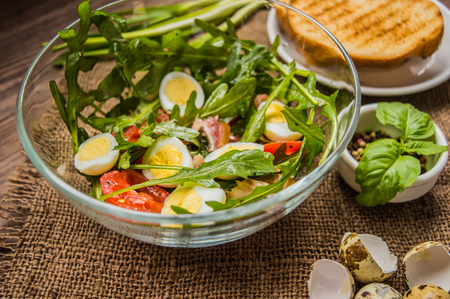 Salad with bacon and arugula. Wooden rustic background. top view. Close-up