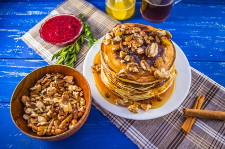 Pancakes with walnuts and maple syrup for breakfast.