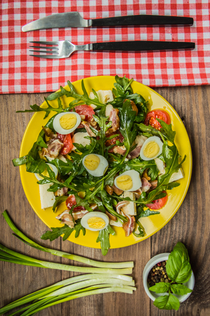 Warm salad with bacon and arugula. Wooden rustic background. top view. Close-up