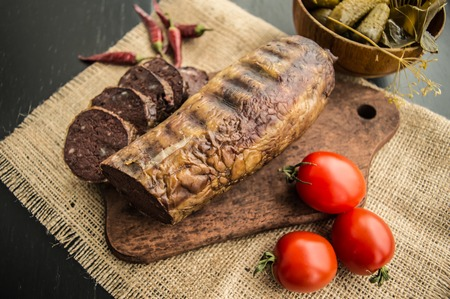 offal: Homemade blood sausage with offal on a black wooden background Stock Photo