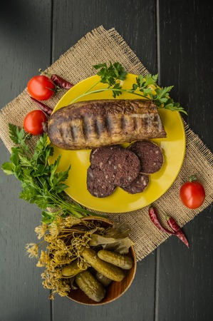 offal: Homemade blood sausage with offal on a black wooden background. top view