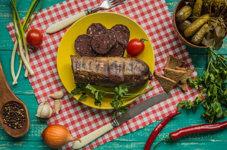 offal: Homemade blood sausage with offal on a turquoise wooden background. top view