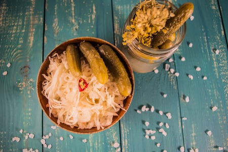 marinated gherkins: Fresh sauerkraut and pickles. At the turquoise wooden background. Top view.