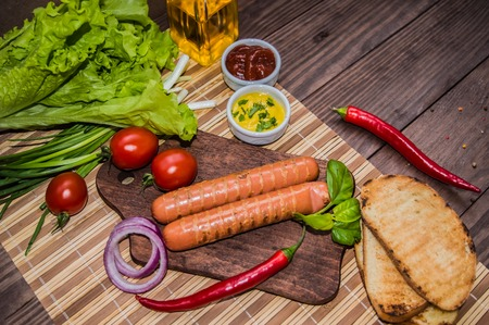 Grilled sausage with pasta, slices of bread, herbs and cherry tomatoes. Top view. On a wooden rustic brown background.