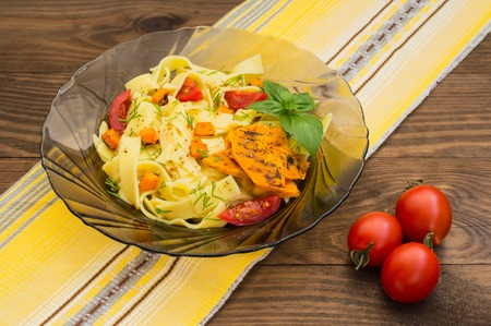 Fettuccine pasta with grilled pumpkin on a wooden table. Close-up