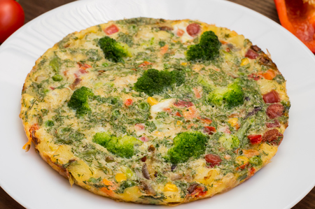 Spanish tortilla on a white plate. Restaurant supply. Wooden rustic table. Top view. Close-up
