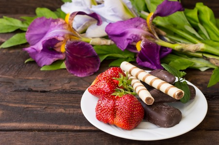 Strawberries with chocolate on a background of flowers. Wooden table