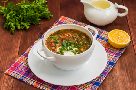 Solyanka, Russian dishes, soup on a steep meat broth with hot spices. Wooden background. Close-up