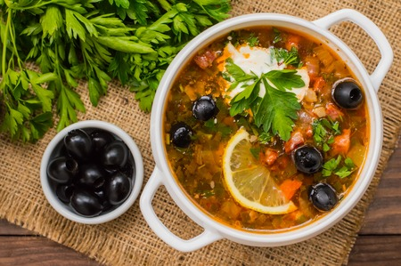 Solyanka, Russian dishes, soup on a steep meat broth with hot spices. Wooden background. Top view. Close-up