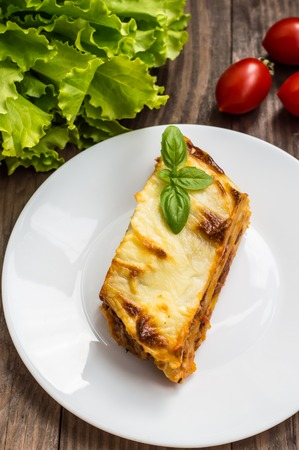 carne picada: Lasagna, traditional Italian food on a wooden background. Close-up Foto de archivo
