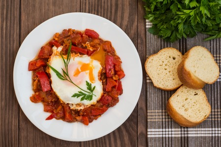 Shakshuka on a white plate. Traditional Jewish dish. Wooden table.