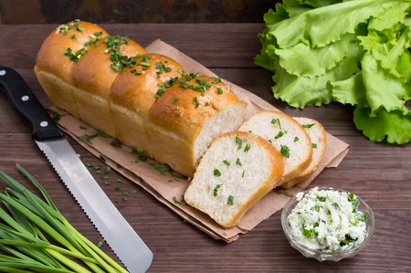 Garlic bread with cheese and herbs on a wooden background Stock Photo