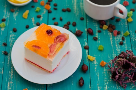 Cake with coffee and sweets with different fruits. Cute and a fabulous breakfast. Turquoise wooden background.