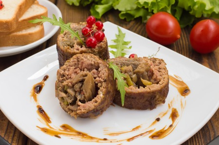 Meatloaf stuffed with mushrooms with sauce and berries. Wooden rustic background. Stock Photo