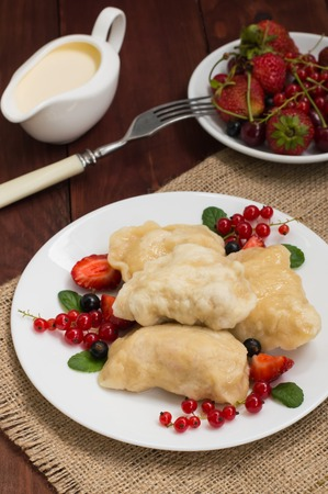 Dumplings with strawberries on a background of wild berries