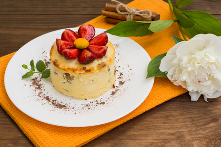Curd pudding with raisins and strawberry. Wooden rustic table. Close-up