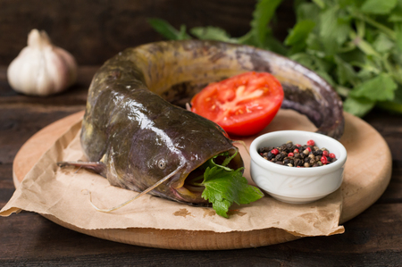 Fresh catfish on a cutting board. Wooden background