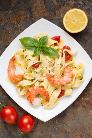 Fettuccine pasta in cream sauce with king prawns on a plate on the wooden table. Top view. Close-up
