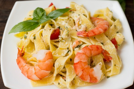 Fettuccine pasta in cream sauce with king prawns on a plate on the wooden table. Horizontal view from above Stock Photo
