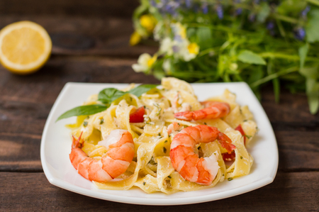 Fettuccine pasta in cream sauce with king prawns on a plate on the wooden table.