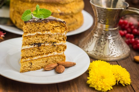 Traditional Hungarian Esterhazy cake .selective focus .Esterhazy cake with chocolate piece with a name of the cake: Esterhazy . Wooden background. Close-up