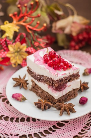 Cherry sponge cake with cream and red currant. Wooden background. Top view. Close-up