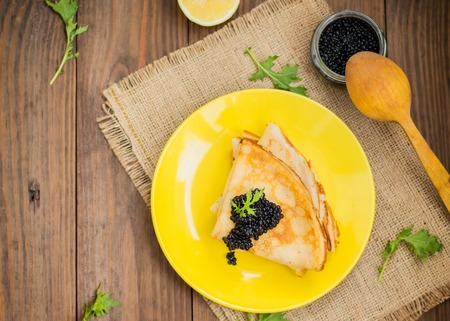 Black caviar on Russian pancakes - blini. Selective focus.