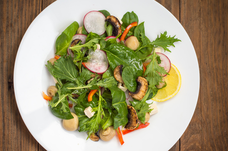 Fresh spring salad with radish, Mizuno, mushrooms grilled, Adygei cheese, spinach, bell pepper, lemon, corn. Wooden background