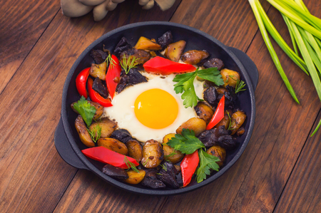 huevos revueltos: baked potato with mushrooms and egg. Wooden background. Top view. Close-up