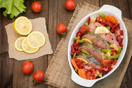 gilthead bream: Sea bass with vegetables. marinated fish with vegetables for cooking in the oven. Wooden background