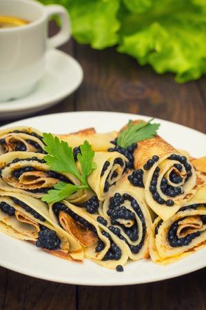 maslenitsa: Rolls pancakes with black caviar. Russian cuisine. Flat lay. Maslenitsa. Wooden background Stock Photo