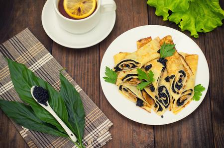 maslenitsa: Rolls pancakes with black caviar. Russian cuisine. Flat lay. Maslenitsa. Wooden background. Top view