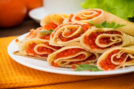 maslenitsa: Rolls pancakes with red caviar. Russian cuisine. Flat lay. Maslenitsa. Wooden background
